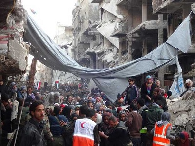 Refugees waiting to be allowed to proceed across the frontline in Yarmouk to join queue at the distribution area. (UNRWA/file)