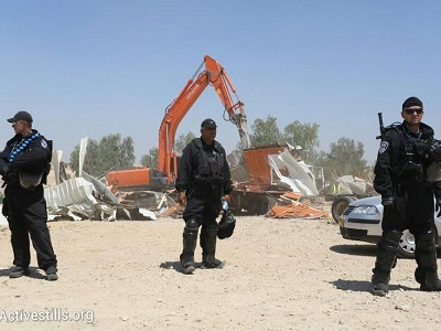 Israeli policemen stand by as a bulldozer demolishes the village of Al-Araqib for the 93rd time in five years. (Activestills.org)
