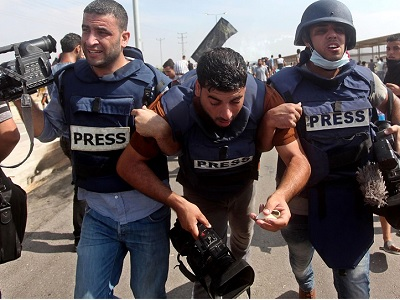 Palestinian journalists help their injure colleague get to safety after being attacked by Israeli soldiers near the Erez Crossing on Oct 13. (Via MEMO)