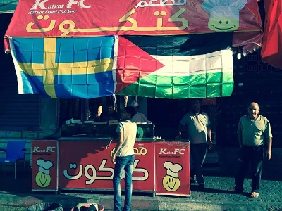 A restaurant owner in Gaza raises the Palestinian Sweden flag to celebrate Swedish recognition as Palestinian state. (Courtesy)