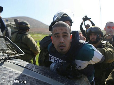 Israeli troops detain a Palestinian journalist at a protest against the illegal settlement outpost of Adei Ad in the northern West Bank. (Photo: Oren Ziv, Activestills.org, file)