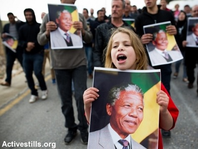 A Palestinian girl carries a picture of Nelson Mandela in the West Bank village of Nabi Saleh. (Photo: Activestills.org, file)