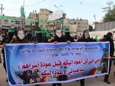 Hamas fighters march in Gaza with the faces of captured Israeli soldiers with a banner reading: 'Mother and father, I will not return to you before Palestinian prisoners return home.' (Photo: via Twitter)