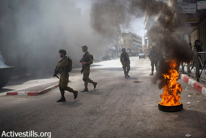 Israeli soldiers throw tear gas at Palestinian couple running with baby